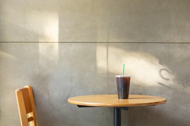 レストランの木製テーブルの上のアイスブラックコーヒーamericanoのプラスチック製のコップを奪う