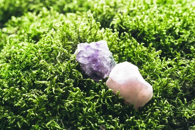 아름다운 이끼 배경에 자수정과 장미 석영. 의식, 명상 및 영적 수행을 위한 마법의 돌. 소프트 포커스입니다.