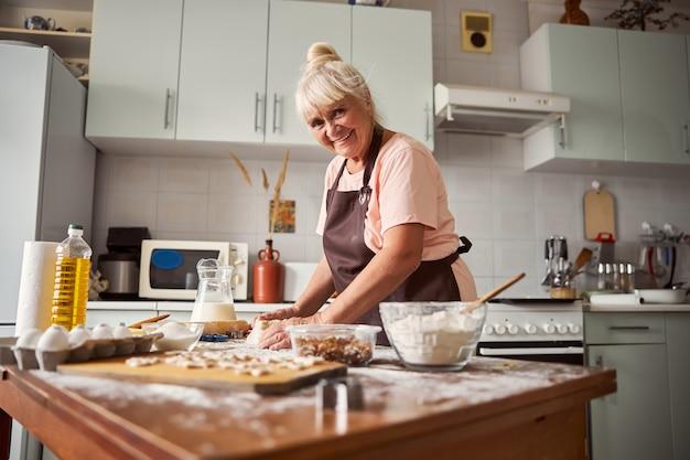 台所のテーブルで食事を準備する友好的な老婆