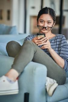 Дружелюбная брюнетка женщина, сидящая в кресле со своим телефоном