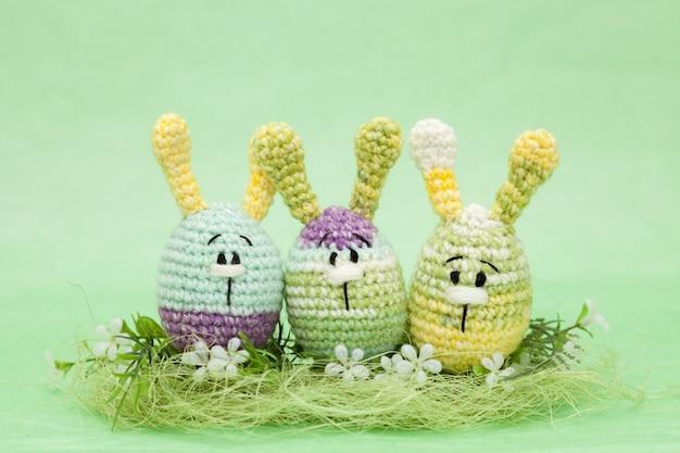 復活祭の装飾の卵、花、緑の背景にバニー、amigurumi