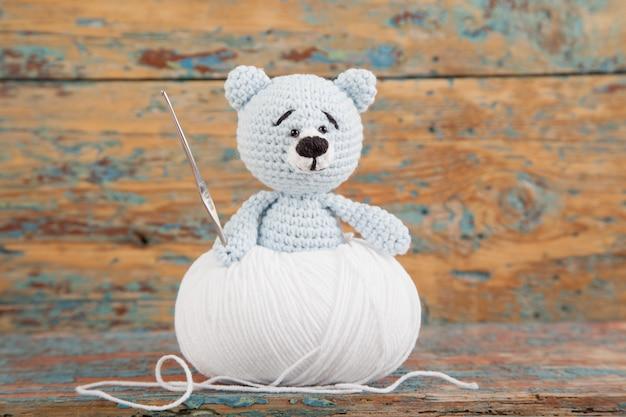 Вязаный маленький мишка на старом деревянном. ручная вязаная игрушка. amigurumi