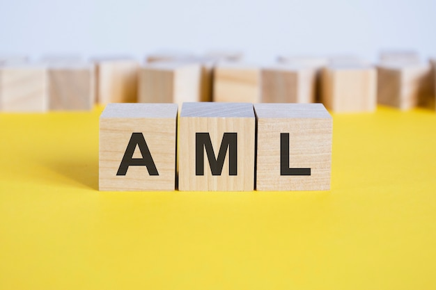 Буквы aml на деревянных блоках, лежащих на желтом столе. блоки игрушки бизнес-концепции с буквами вокруг. выборочный фокус