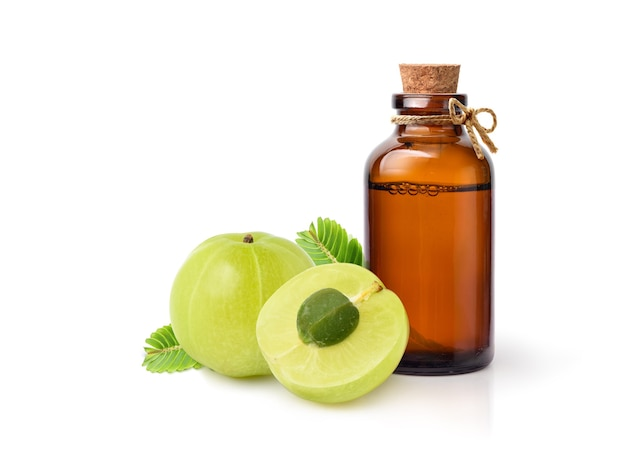 Amla (indian gooseberry) essential oil extract in amber bottle with fruits and leaves isolated on white.