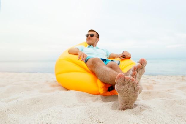 Красивый веселый amn наслаждаясь досугом, лежа на воздушном диване lamzac и слушая музыку