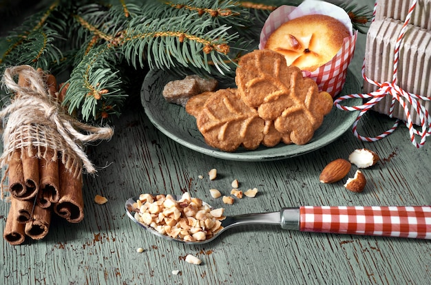 Amond cookies and lemon mini-muffin with ingredients and christmas tree twigs