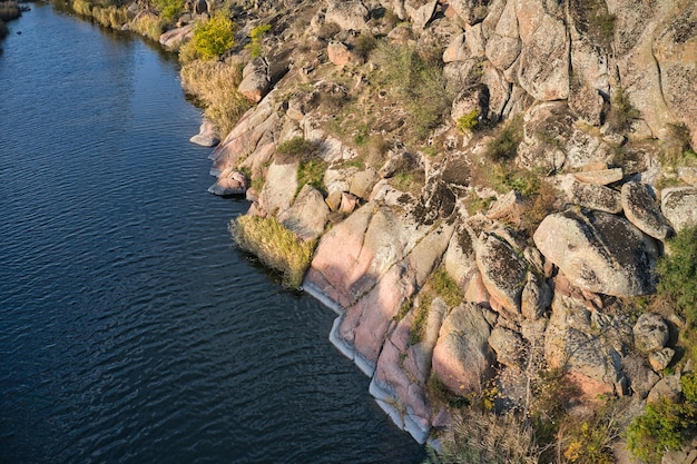 Among the large boulders, a smooth shining stream flows in the evening warm light in picturesque ukraine.