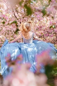 분홍 향기로운 사쿠라 사이에서 파란 드레스를 입은 아름다운 여성이 사과나무를 배경으로 달리고 있다