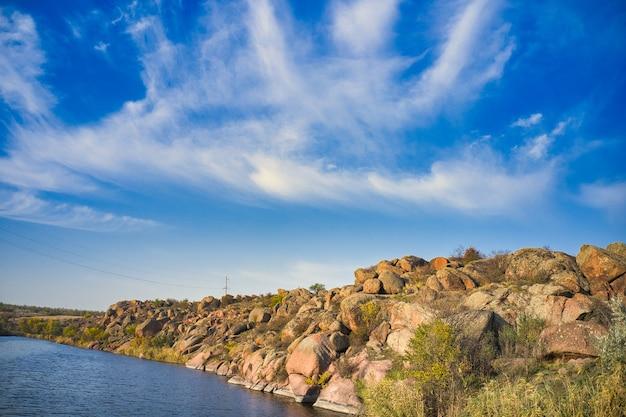 Среди больших валунов плавный сияющий ручей течет в теплом вечернем свете живописной украины.