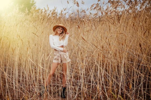麦わら帽子の興奮した金髪の幸せなサファリスタイルの女の子は、amongの中で自然を歩きます。