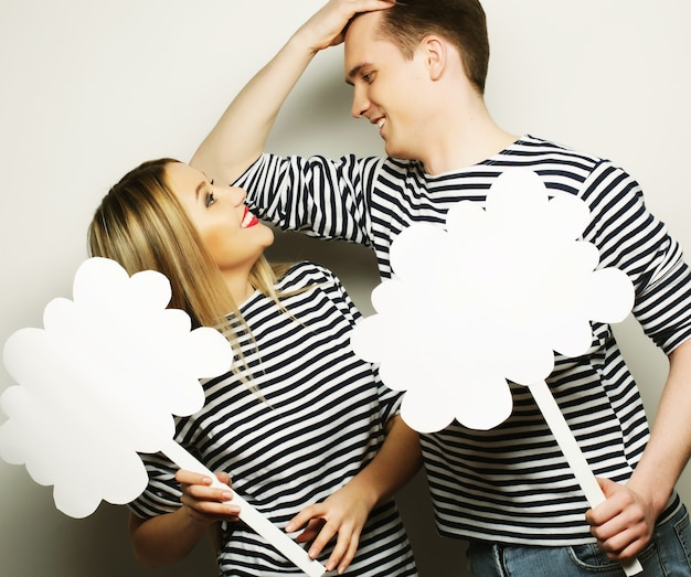 Amorous couple holding blank paper on stick