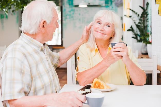 Amorous senior couple sitting in cafe