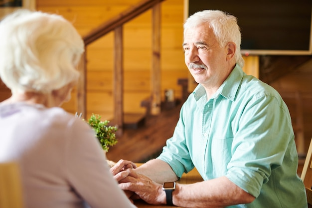 Влюбленный пожилой мужчина смотрит на жену во время разговора за столом на кухне или в гостиной дома