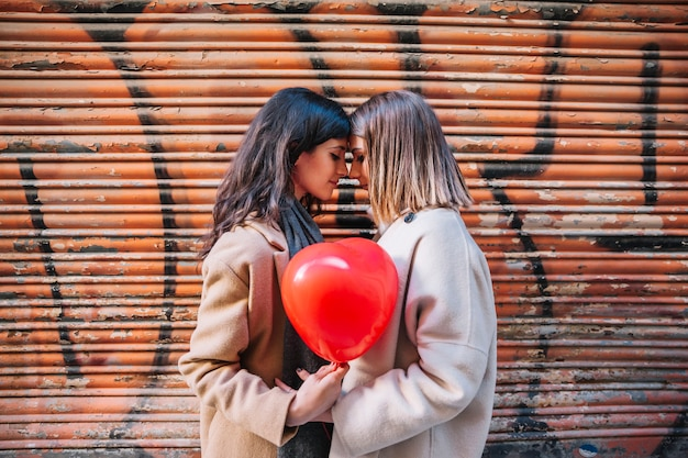Amorous young girlfriends posing with balloon