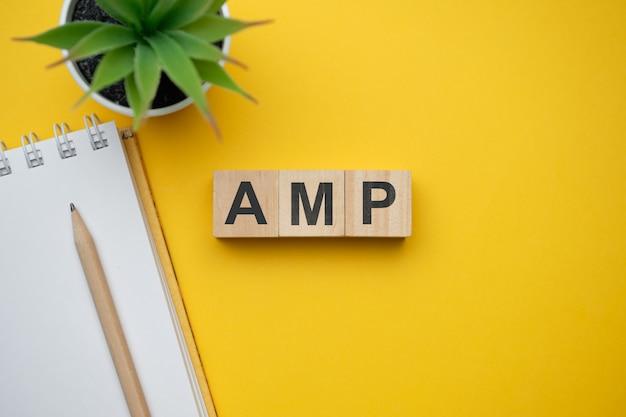 最新のマーケティング流行語amp-accelerated mobile pages。ブロックと木製のテーブルの上から見る。上面図。
