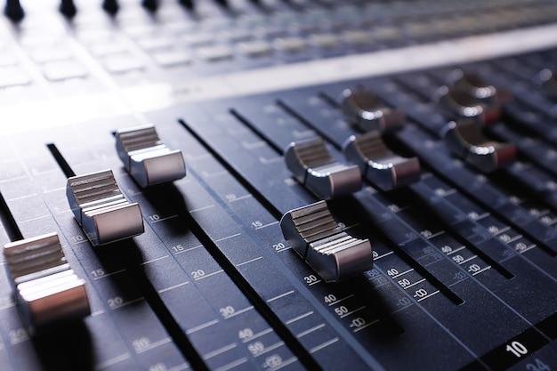 Amplifying equipment, studio audio mixer knobs and faders.