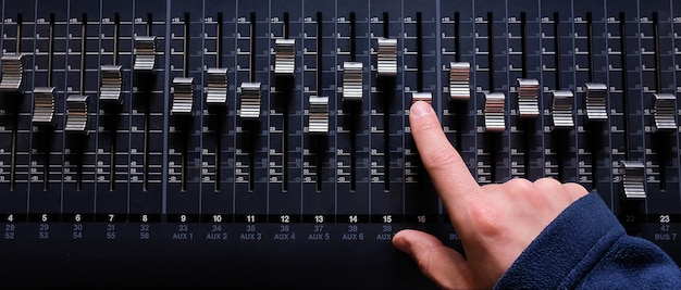 Amplifying equipment that adjusts studio audio mixer knobs and faders. workplace and equipment of the sound engineer. acoustic mixing of music, selective focus.