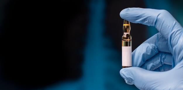 Ампула в руках, пустой бланк для текста. вакцина на фоне рентген легких