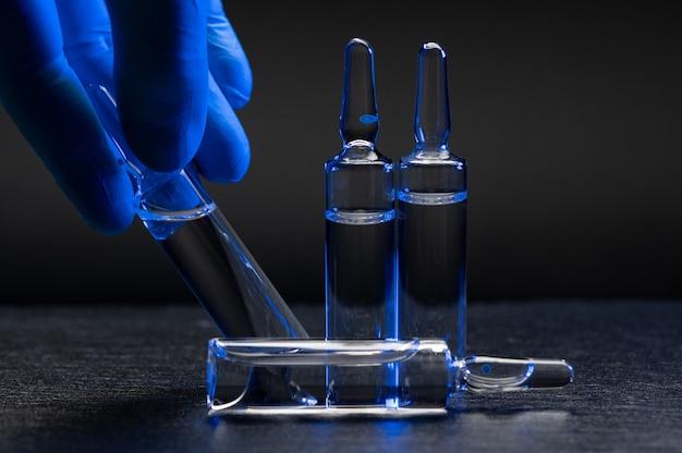 ゴム手袋をはめた医療従事者の手にワクチンを入れたアンプル