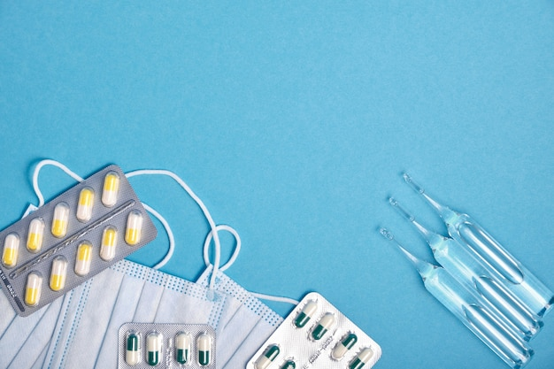 Ampoules, blisters with pills and capsules and medical protective masks on a blue background copy space top view