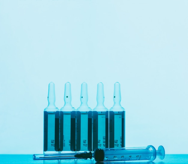 The ampoules with solution for injections and disposable syringe on a blue background