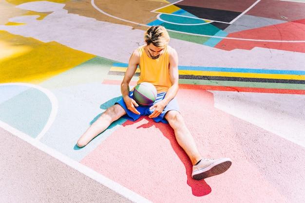 公園でバスケットボールをし、スポーツをしている切断された少年。障害と持続性についての概念