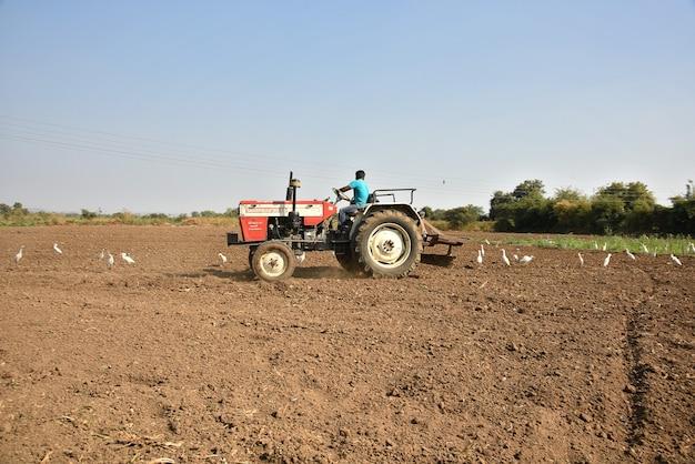 Амравати, махараштра, индия - 3 февраля 2017 г .: неизвестный фермер в тракторе готовит землю для посева с культиватором семенного ложа.