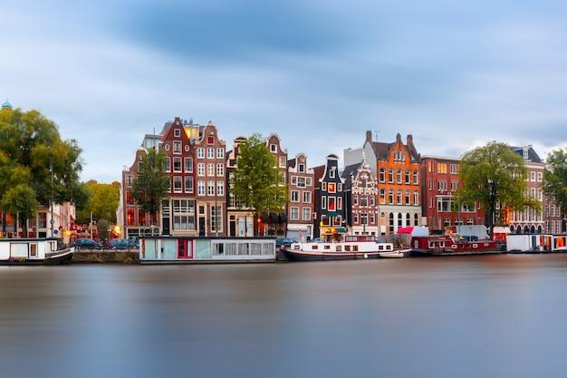 Амстердамский канал амстел с типичными голландскими домами и плавучим домом с лодки утром, голландия, нидерланды.
