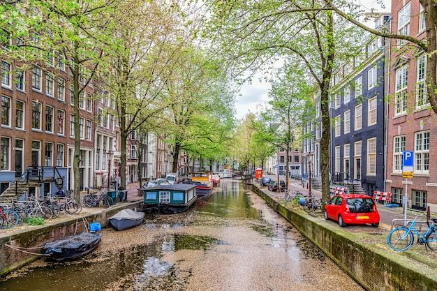 봄날 암스테르담 운하 보트와 중세 전형적인 네덜란드 주택 암스테르담 네덜란드