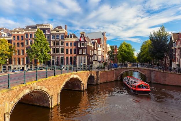 암스테르담 운하 reguliersgracht는 전형적인 네덜란드 주택, 다리 및 화창한 아침, 네덜란드, 네덜란드 동안 하우스 보트.