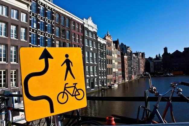 Вид на канал амстердама с табличкой для велосипеда, недалеко от центра города