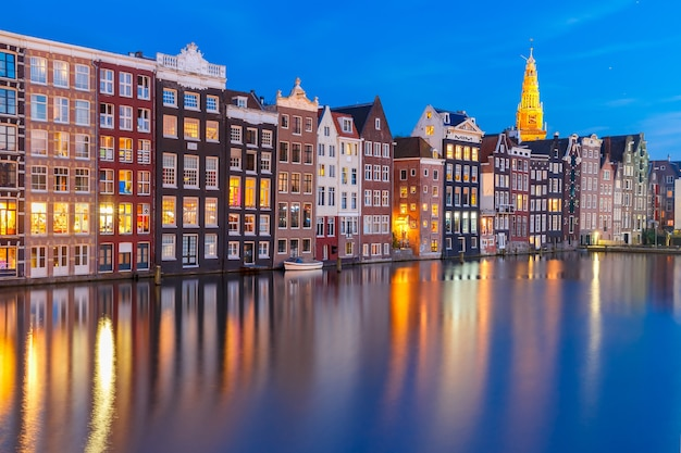 Amsterdam canal with beautiful typical dutch dancing houses and oude kerk church during twilight blue hour, holland, netherlands