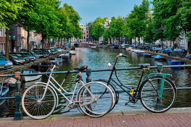 Канал амстердам с лодками и велосипедами на мосту