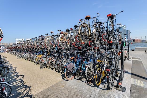 암스테르담, 네덜란드 -8 월 01 : 암스테르담 중앙역. 2012 년 8 월 1 일 네덜란드 암스테르담에서 중앙역 앞에 많은 자전거가 주차되었습니다.