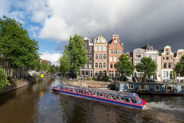Amsterdam, netharlands - july 5, 2016 : tourists in cruise boat at amsterdam canal, netherlands.