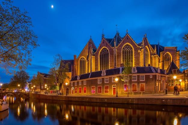 암스테르담, 네덜란드 - 2107년 5월 2일: tranditional 교회 전화 builiding 타워 지역 관광 사람들이 황혼의 시간에 방문하는 oude kerk.
