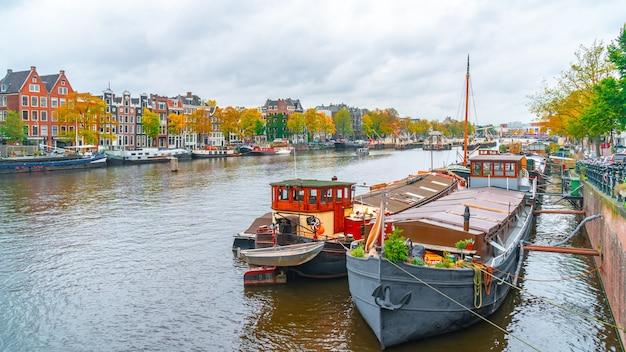 암스테르담, 네덜란드-2019 년 10 월 15 일 : 암스테르담 운하의 다채로운 주택과 보트. 암스테르담의 가을. 여행