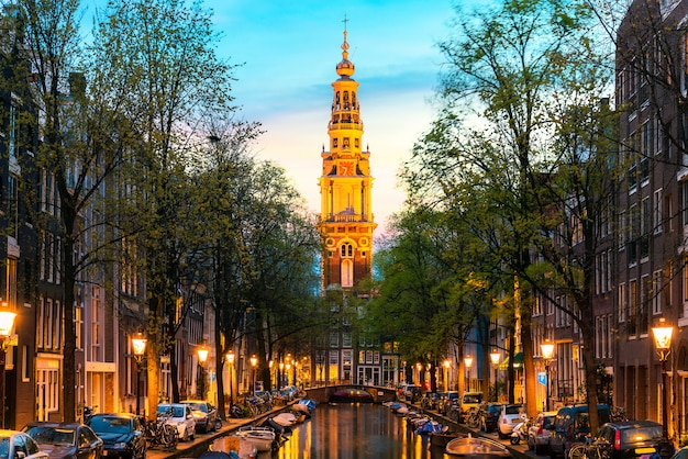 Amsterdam zuiderkerk church tower at the end of a canal in the city of amsterdam, netherlands at night .