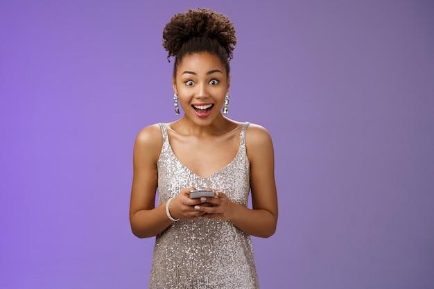 은빛으로 반짝이는 드레스를 입은 아프리카계 미국인 소녀는 문자 메시지를 통해 놀라운 소식을 받고 놀라서 스마트폰을 들고 서 있는 믿을 수 없는 행운을 보며 행복하게 웃고 있습니다.