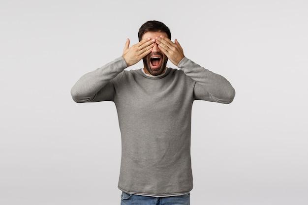 회색 스웨터에 즐겁고 평온한, 행복 잘 생긴 수염 난 남자, 손바닥으로 눈을 감고 미소를 지으며, 놀람을 기다리고, 선물을보고, 까 playing 놀이, n 탐색 숨기기