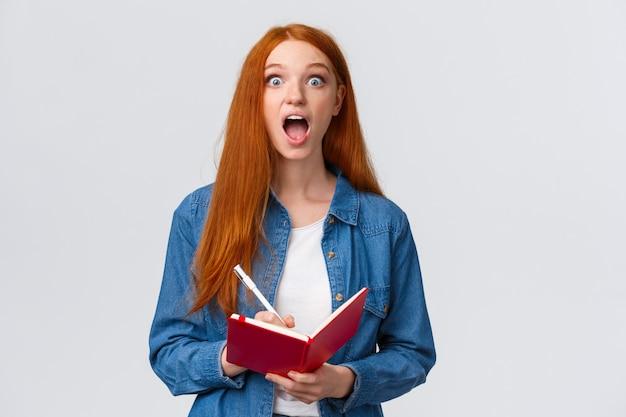 Удивленная и взволнованная, изумленная рыжая девушка, очарованная удивительной лекцией, произносит речь, записывает полезные заметки, держит блокнот и смотрит в восторг