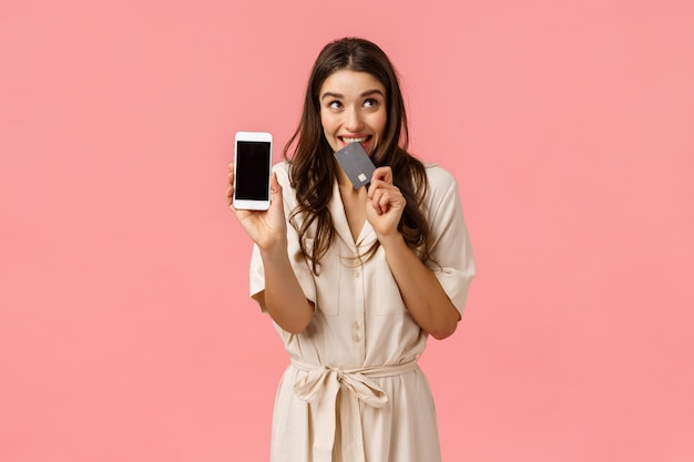 Удивленная и взволнованная милая девушка шоппоголик не может дождаться доставщика, заказать онлайн, кусать кредитную карту, держать смартфон, показывать экран мобильного телефона и смотреть в сторону мечтательно, как тратить деньги