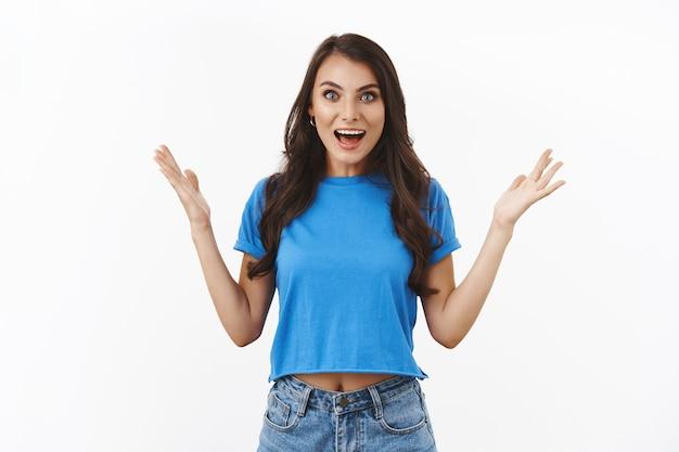 Веселая и взволнованная, удивленная девушка, слышащая подругу, отлично справилась, поздравляю, хвалят члена команды, хорошую работу, отличное достижение, стоит белая стена