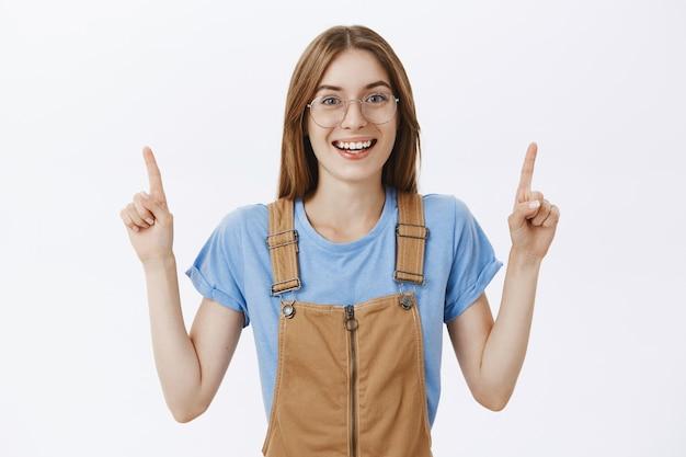 Веселая и заинтересованная красивая девушка в очках показывает пальцем вверх на хорошее промо-предложение