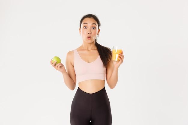 Забавная и удивленная милая азиатская девушка любит заниматься фитнесом и есть здоровую пищу, держит в руках яблочный и апельсиновый сок, выглядит изумленно, говоря: «вау»