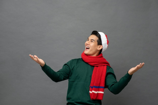 Amused asian man wearing christmas theme clothes with open palms gesture