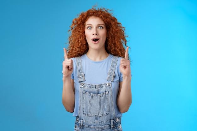놀라움을 금치 못하는 귀여운 빨간 머리 곱슬머리 소녀가 입을 벌리고 턱을 헐떡이며 흥분한 응시 카메라가 흥분된 검지 손가락을 가리키며 흥분된 멋진 가게가 판매 파란색 배경을 제공합니다.