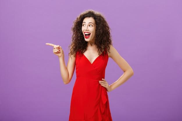 호화로운 빨간 드레스와 곱슬머리 헤어스타일을 하고 저녁 화장을 한 매력적인 유럽 여성은 보라색 배경 위에 흥미롭게 왼쪽을 바라보며 즐겁게 웃고 있습니다.