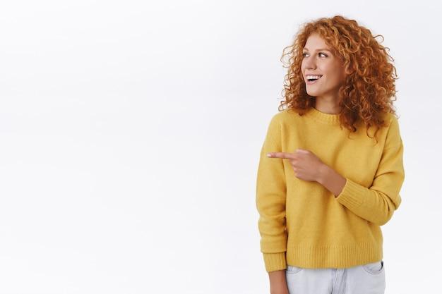 白いセーターを着た面白くて魅力的な赤毛の柔らかい巻き毛の女の子、パーティーに出席し、友達と人差し指を見て、左に曲がり、不思議で幸せな笑顔、クールなイベントをチェックアウト、白い壁