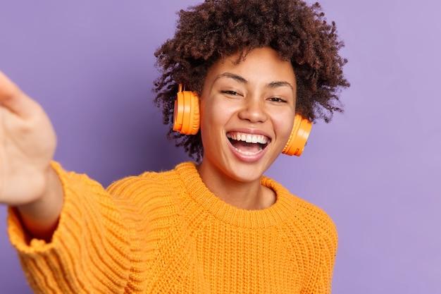 面白がって美しいアフリカ系アメリカ人の女性が腕を伸ばして自分撮りを笑いながらワイヤレスヘッドフォンで音楽を聴いて楽しんでいますオレンジ色のニットセーターのポーズを着ています
